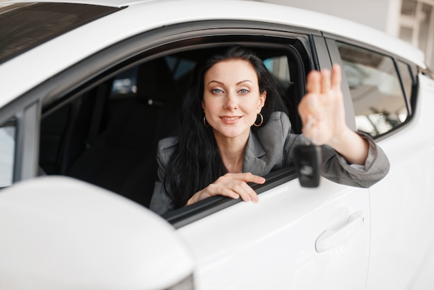 Happy woman shows the key to the new car in showroom. female customer buying vehicle in dealership, automobile sale