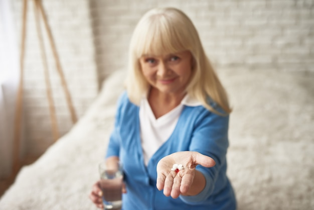 Happy woman shows pills in hand menopause.