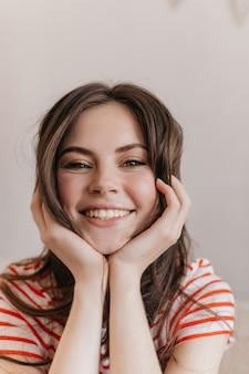 Счастливая женщина искренне улыбается, смотрит вперед и нежно касается ее лица