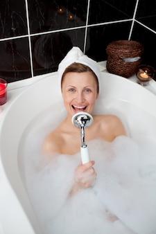 Happy woman singing in a bubble bath
