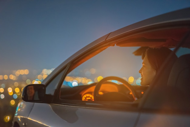 The happy woman sit in a car on the city light background. evening night time