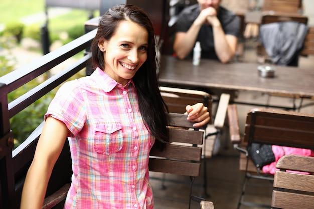 Счастливая женщина сидит на коричневом стуле в летнем кафе.