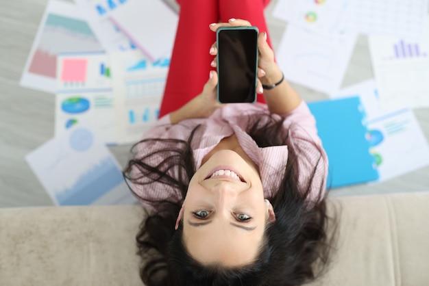 Счастливая женщина сидит на полу, положив голову на диван. женская рука держит экран телефона вверх