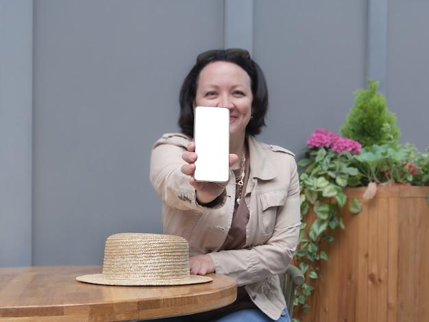 幸せな女性はカフェのテーブルに座って、電話の白い画面を表示します。