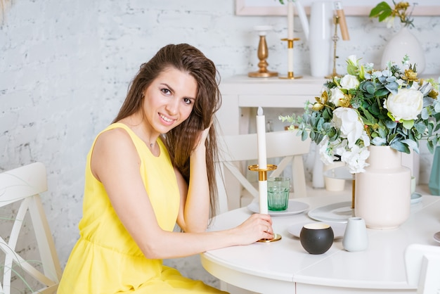 幸せな女性は、黄色のドレスを着てテーブルに座って、美しい花束と燭台があります...