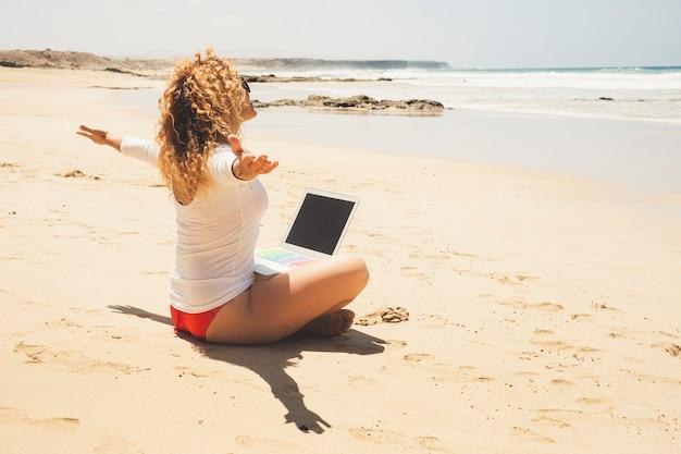 幸せな女性は足にラップトップコンピューターを持ってビーチに座る