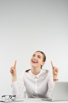 Happy  woman sits next a laptop and laughing looks up pointing fingers up on her both hands. - vertical image