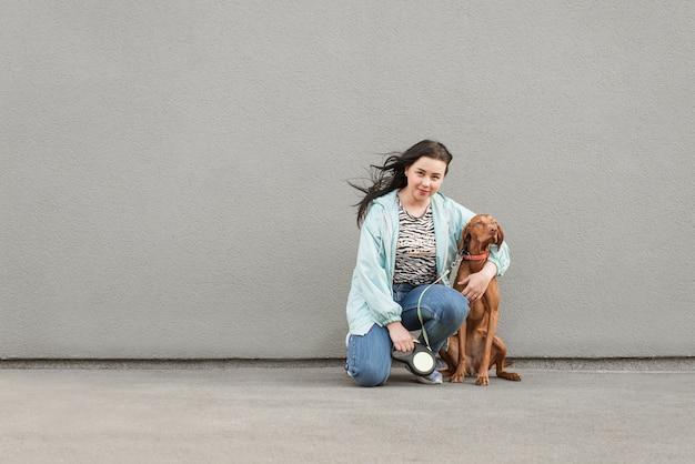 幸せな女は犬と一緒に座っているし、灰色の壁を抱擁