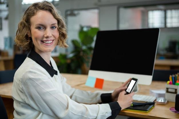 携帯電話を保持している机に座って幸せな女
