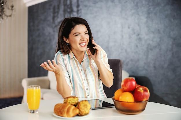 朝、ダイニングテーブルに座って電話を使用して幸せな女性。上司と電話をしている忙しい女性。