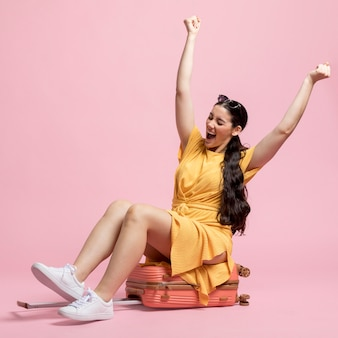 Happy woman sitting on baggage
