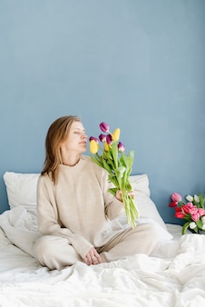 Happy woman sitting on the bed wearing pajamas holding tulip flowers bouquet, blue wall background