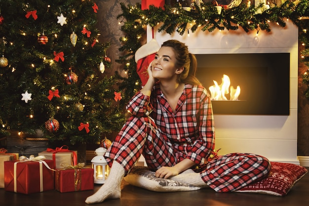 Happy woman sitting beside the fireplace in christmas decorations