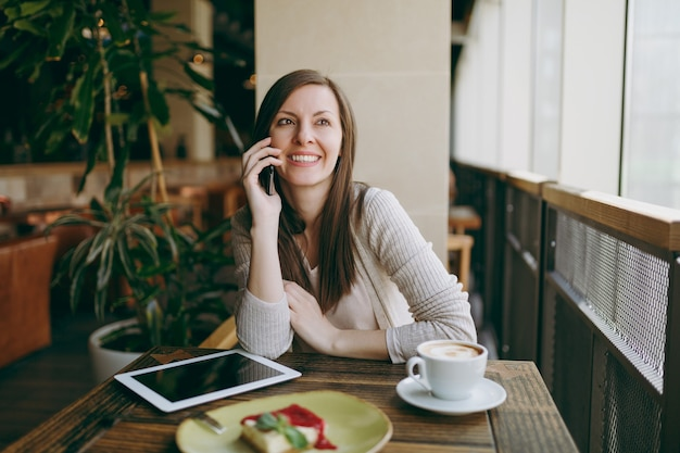 Happy woman sitting in coffee shop with cup of cappuccino, cake, talking on mobile phone, relaxing in restaurant during free time. female working on pc tablet computer rest in cafe. lifestyle concept.