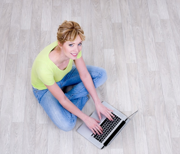Happy woman  sitting on the floor with laptop - high angle view