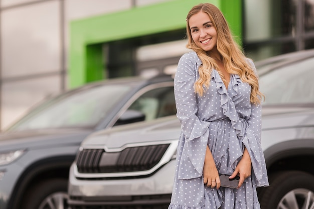 Happy woman sitting in front of a car