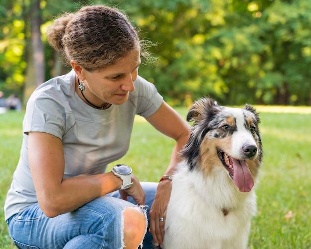 Счастливая женщина сидит, обнимая с молодой красивой австралийской овчаркой на лугу Premium Фотографии