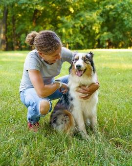 Счастливая женщина сидит, обнимая с молодой красивой австралийской овчаркой на лугу