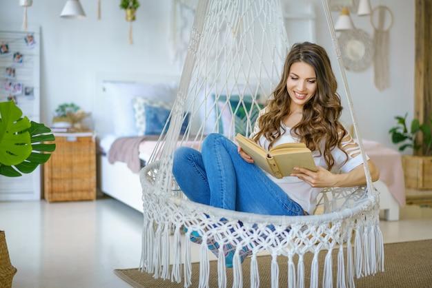 Счастливая женщина сидит в вязаном гамаке в комнате
