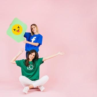 Счастливая женщина, сидя перед ее другом с подмигивающим emoji речи пузырь