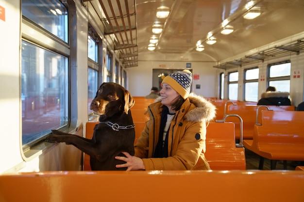 그녀의 사랑스러운 강아지와 함께 지역 기차에 앉아 행복 한 여자는 함께 여행, 창을 통해 보이는