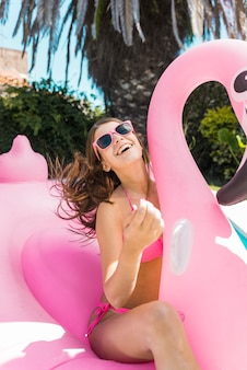 Happy woman sitting on inflatable pink flamingo