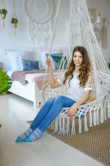 Happy woman sitting in a knitted hammock in the room