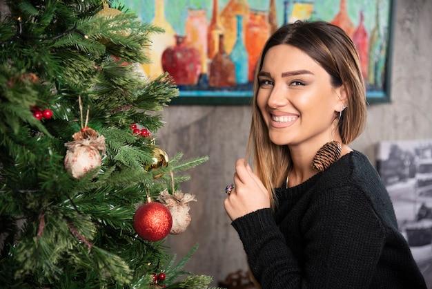 Una donna felice seduta vicino al bellissimo albero di natale. foto di alta qualità