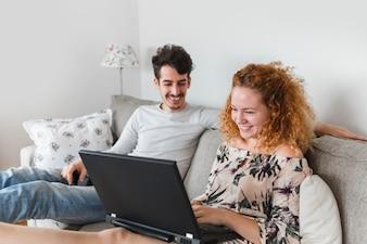 Happy woman sitting near her husband using laptop