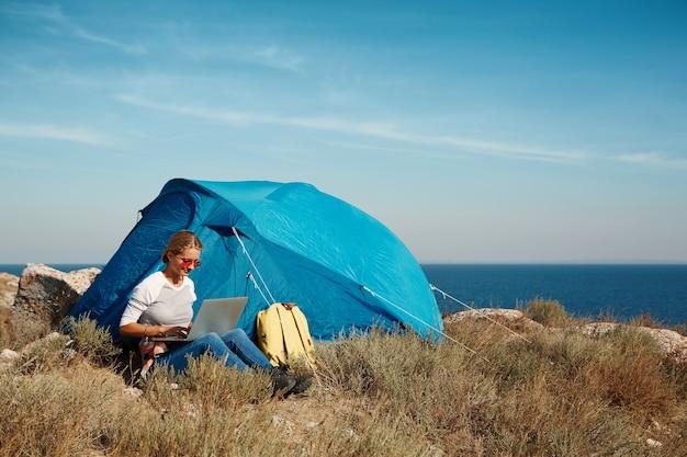 노트북으로 텐트 근처에 앉아 행복 한 여자
