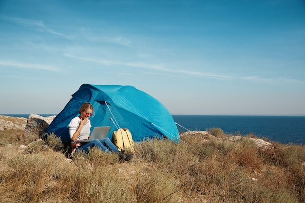 Happy woman sitting near tent with laptop