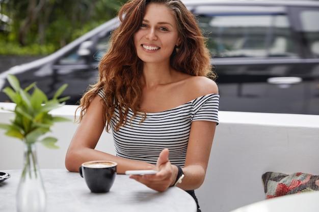 Счастливая женщина, сидящая в кафе