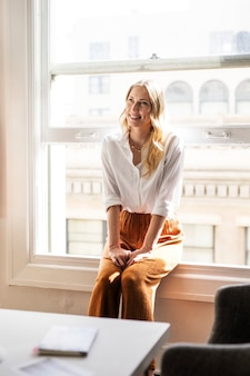 窓枠に座っている幸せな女性