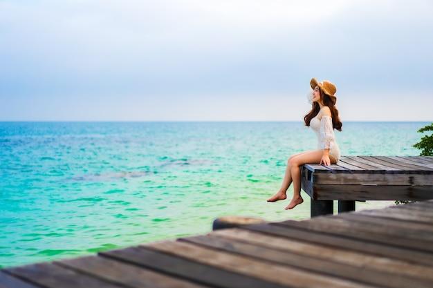 タイ、ラヨーン、コマンノーク島の海のビーチの木造橋に座っている幸せな女性