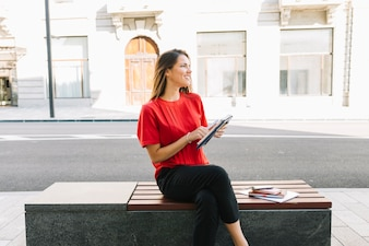 Happy woman sitting on bench with diary