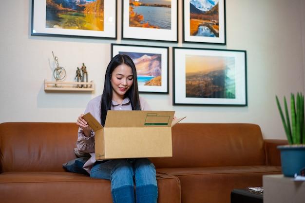 自宅のソファに座って幸せな女カートンボックスを開く
