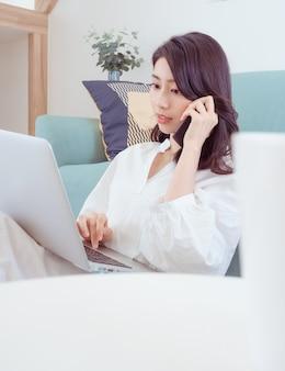 Счастливая женщина, сидя на диване в гостиной дома одна, набрав в чате с помощью компьютера и разговаривая по телефону.