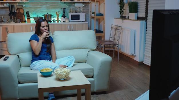 집에서 텔레비전으로 영화를 보고 소파에 앉아 행복 한 여자. 팝콘을 먹고 있는 텔레비전 앞의 편안한 소파에 앉아 저녁을 즐기고 있는 잠옷을 입은 흥분되고 재미있고 외로운 여성.