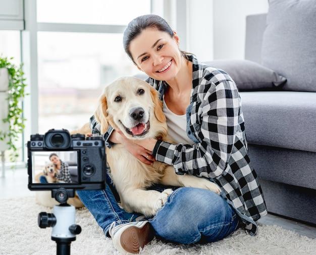 屋内で愛らしい犬と一緒に床に座っている幸せな女性