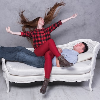 Happy woman sitting on man on sofa