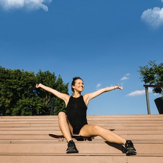 Happy woman sitting on skateboard raising her arms
