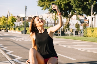 Happy woman sitting on skateboard taking selfie with cellphone