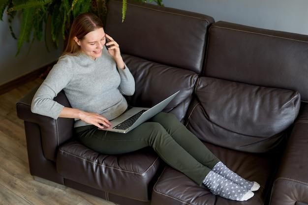 ラップトップとソファに座って、自宅で電話で話している幸せな女性。ノートパソコンと電話を使用して勉強している大学生。