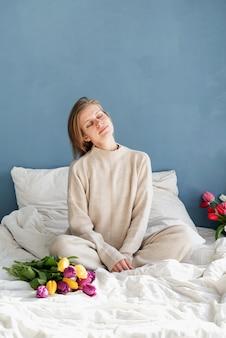 チューリップの花の花束、青い壁の背景を保持しているパジャマを着てベッドに座っている幸せな女性