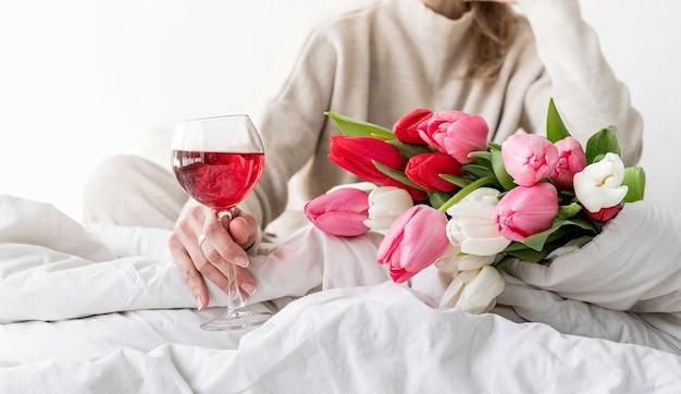 花と赤ワインのグラスを楽しんで、パジャマを着てベッドに座っている幸せな女性