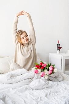 花を楽しんだりストレッチしたりして、パジャマを着てベッドに座っている幸せな女性
