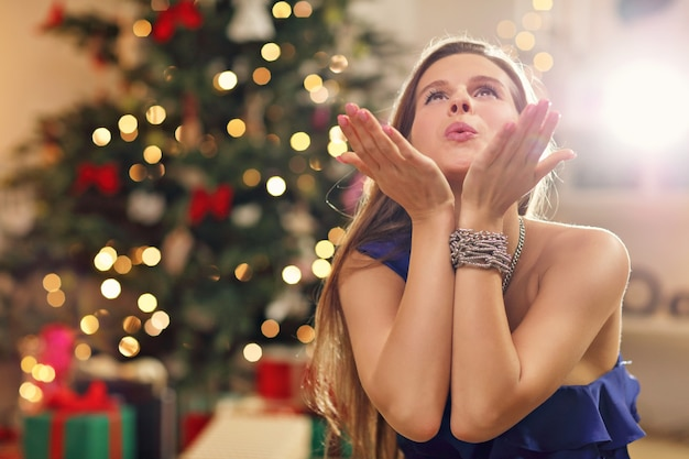 クリスマスツリーの上に座っている幸せな女性