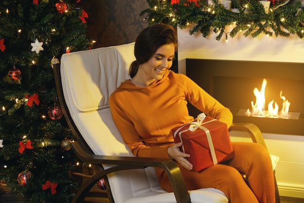Happy woman sitting in the rocking chair beside fire place