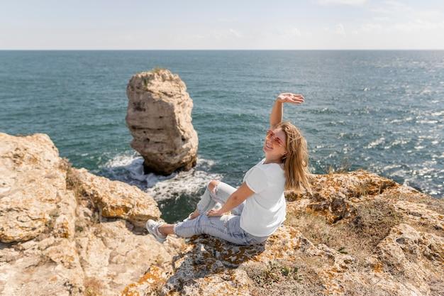 Happy woman sitting on rocks
