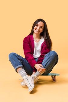 Happy woman sitting on skateboard